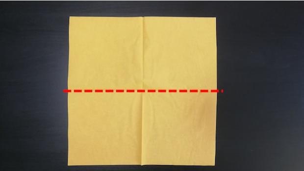 1) Legen Sie eine Serviette offen auf den Tisch und falten Sie sie einmal mittig, sodass sie jetzt halb so groß ist