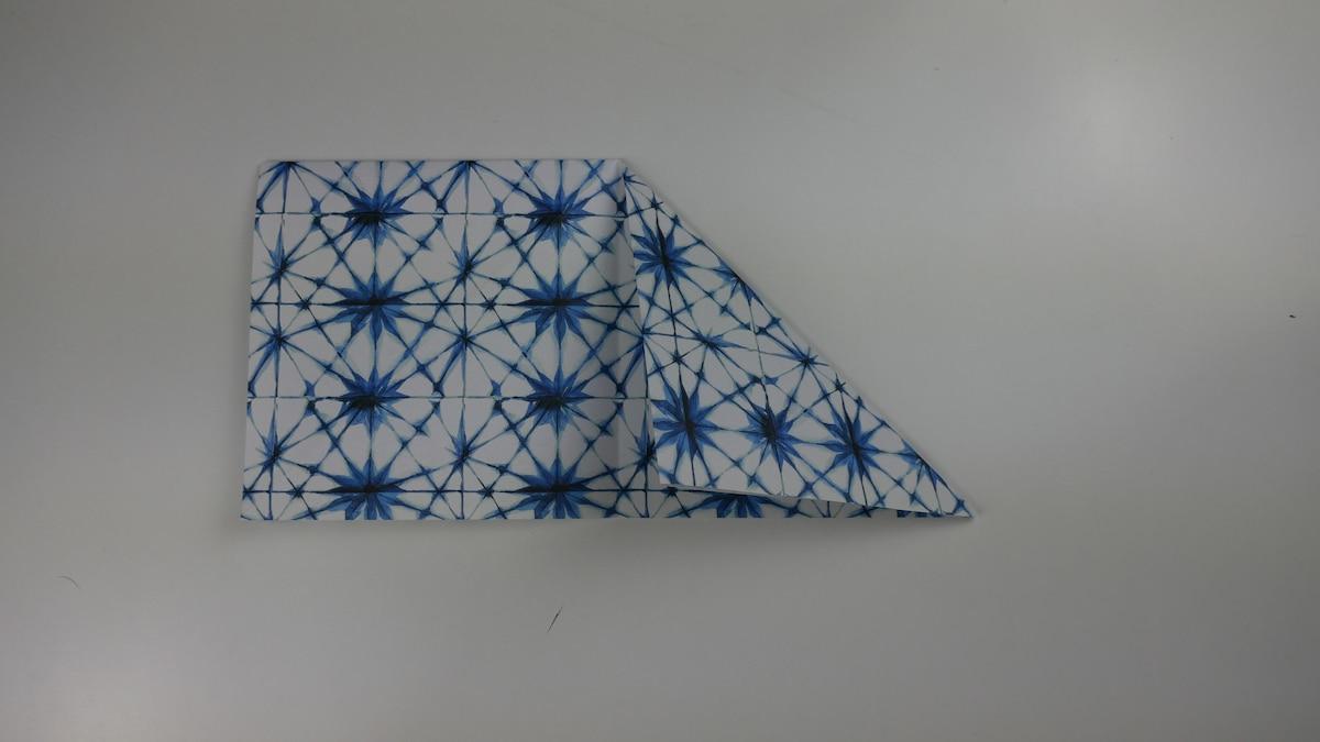 Falten Sie das Quadrat in der Mitte und schlagen auf der einen Seite die Ecke nochmals in beide Richtungen ein.