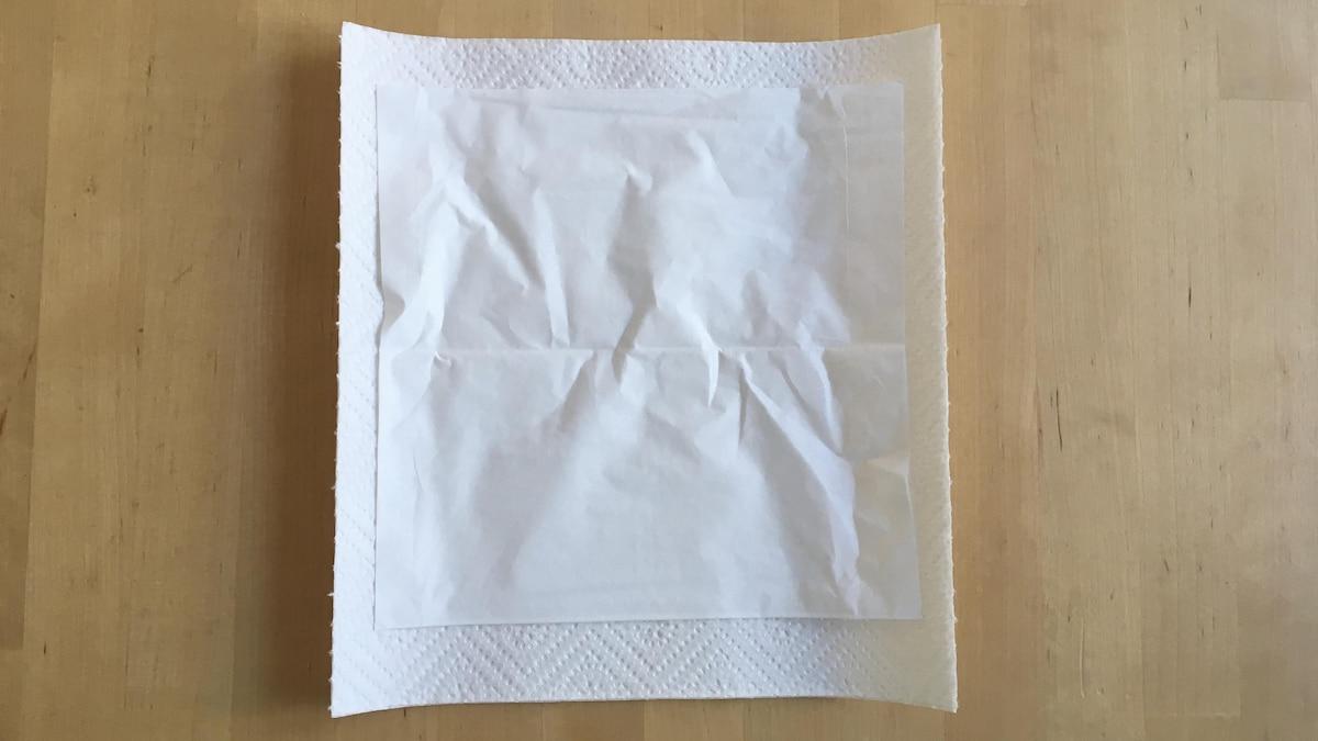 Legen Sie zwei Blätter Küchenrolle und ein Papiertaschentuch übereinander