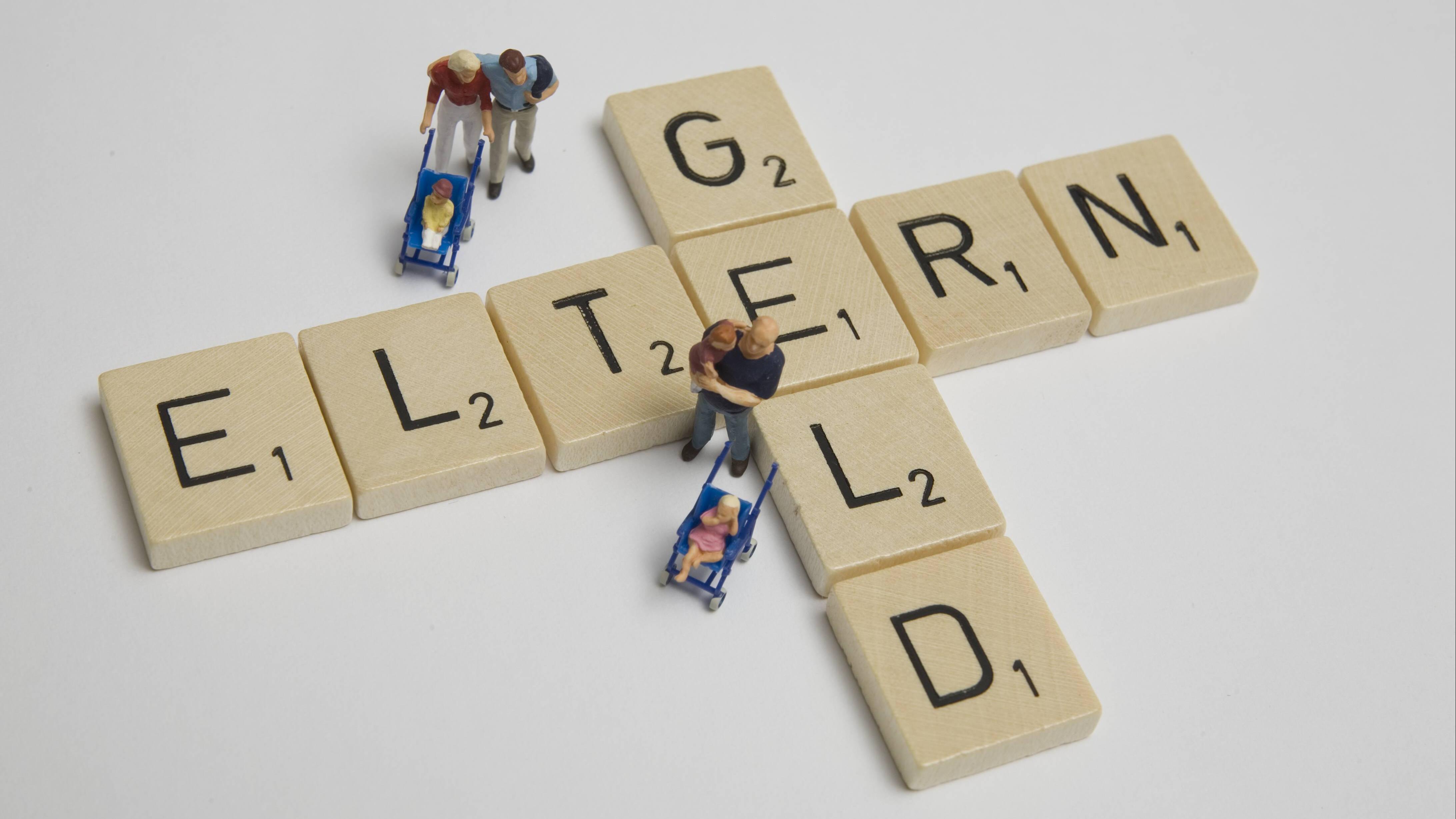 Elterngeld - Schriftzug aus Scrabblesteinen mit Spielfiguren