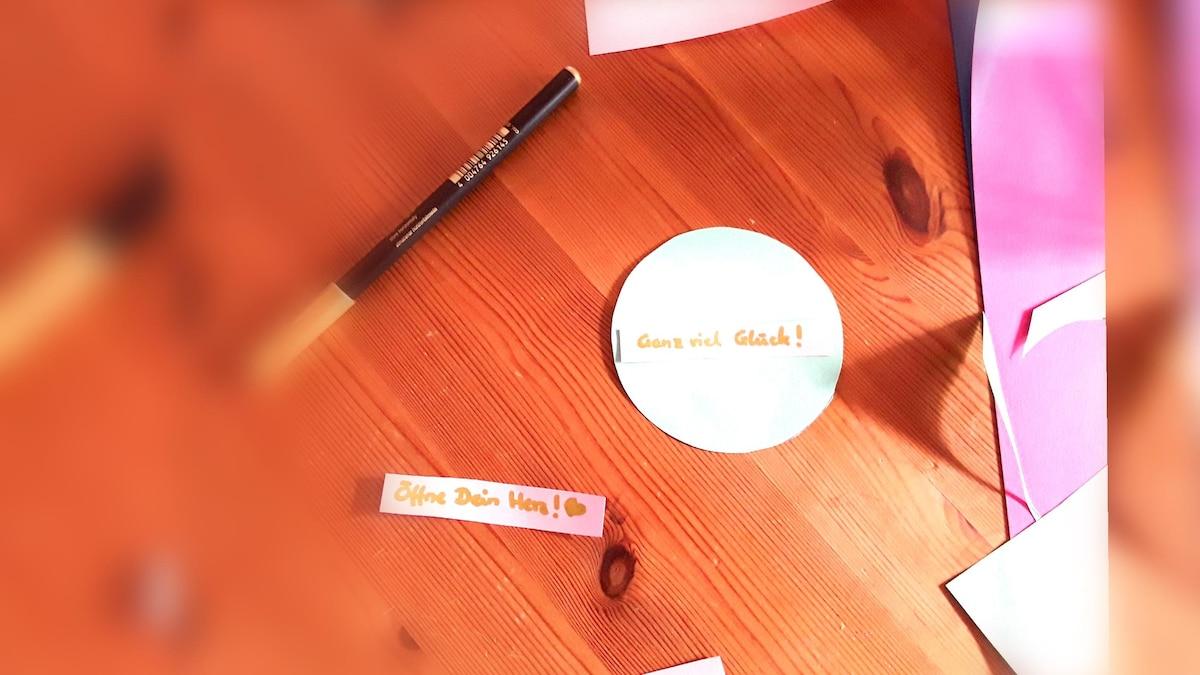 Schneiden Sie einen kleinen Zettel aus und beschriften sie ihn. Der Zettel sollte nicht größer sein als der Kreis