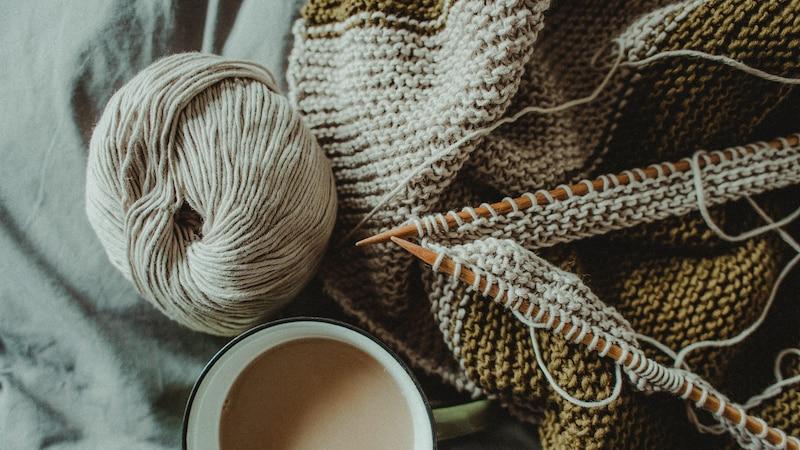 Eine Wolldecke kaufen oder selber machen? Mit Stricken oder Häkeln lässt sich aus Wollresten schnell eine Decke anfertigen.