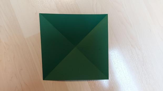 Falten Sie die gegenüberliegenden Seiten des Papierbogens diagonal zueinander.
