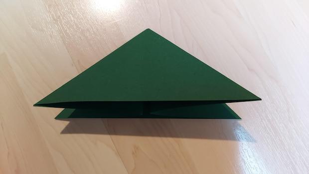 Klappen Sie die Außenseiten jeweils nach innen, so dass ein Dreieck entsteht.
