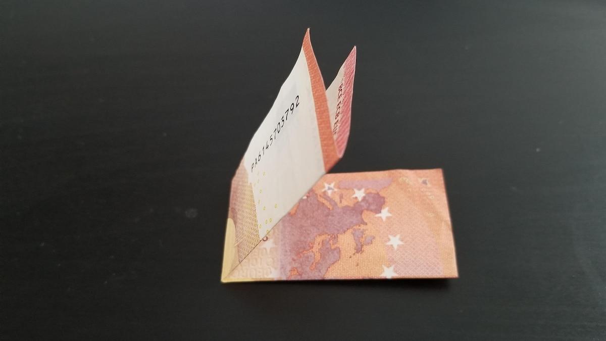 Legen Sie den Geldschein dann quer um.