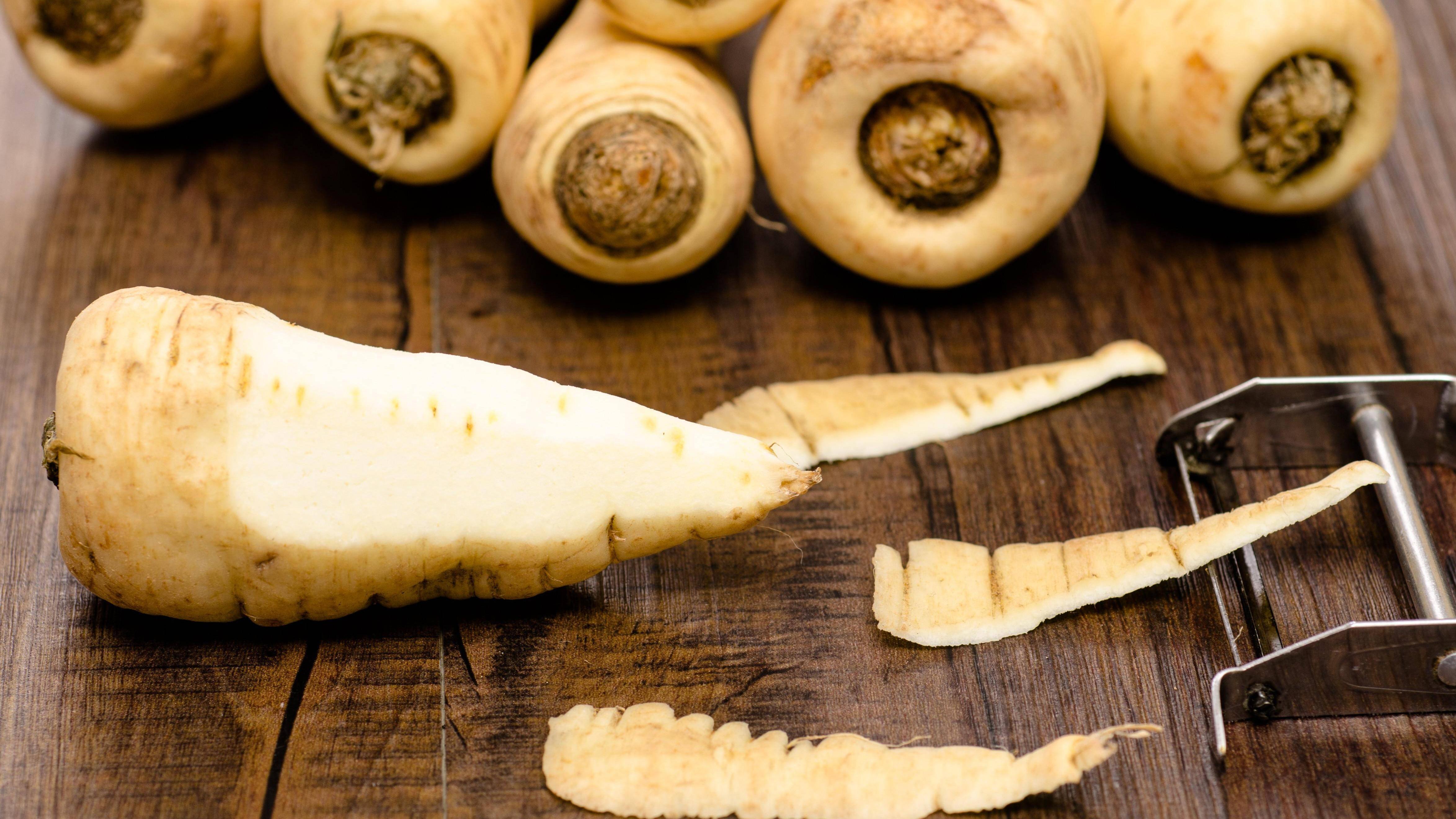 Für ein saisonales Rezept mit gebackenen Pastinaken müssen Sie das Wurzelgemüse zunächst mit einem Sparschäler schälen.