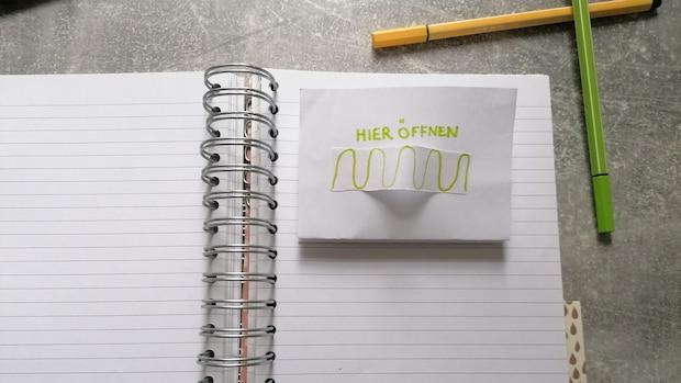 Klappen Sie den Papierstreifen zusammen und kleben Sie ihn an der Unterseite in Ihr Scrapbook.