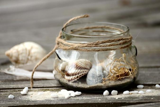Als Erinnerung an den Urlaub können Sie ein Einmachglas mit Strandsand und Muscheln dekorieren.