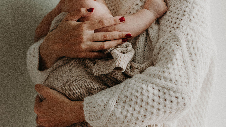 Stützen Sie Ihr Baby beim Tragen ohne Tragehilfe, um ein Zusammensacken zu vermeiden.
