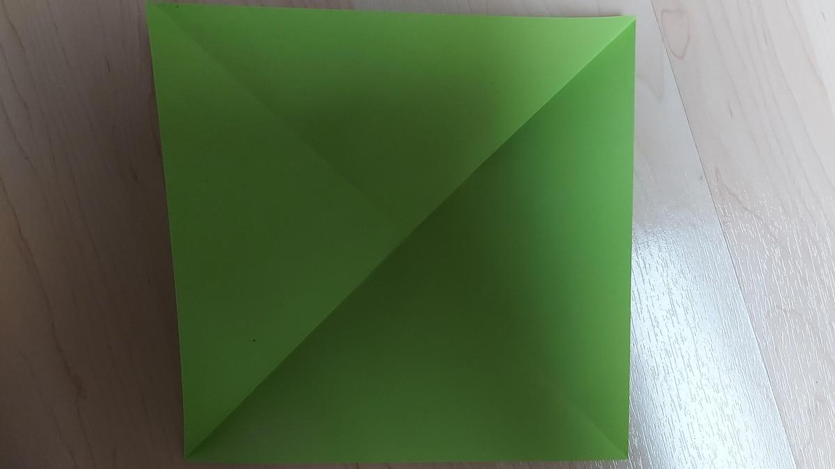 Baum in 3D basteln: 1. Legen Sie das Buntpapier vor sich hin, falten Sie jeweils die gegenüberliegenden Seiten diagonal zueinander und wieder auf.