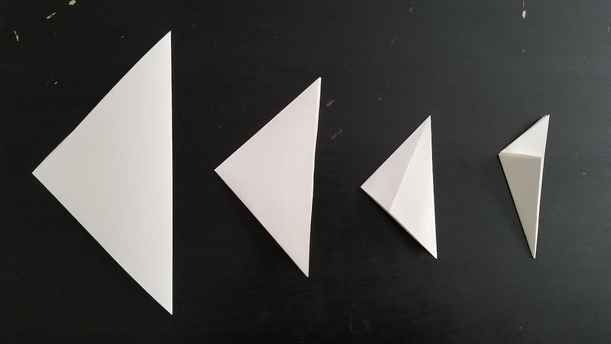 Winterdeko basteln: Falten Sie das Papier dreimal zu einem Dreieck.