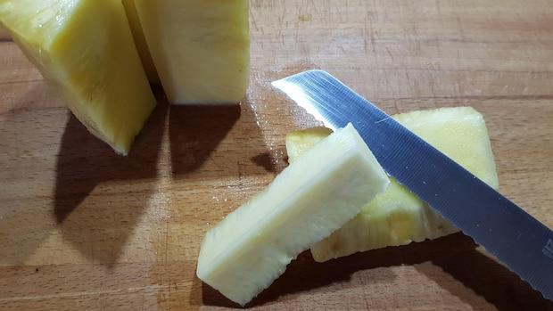 Die geschälte Ananas wird geviertelt, bevor der Strunk entfernt wird.