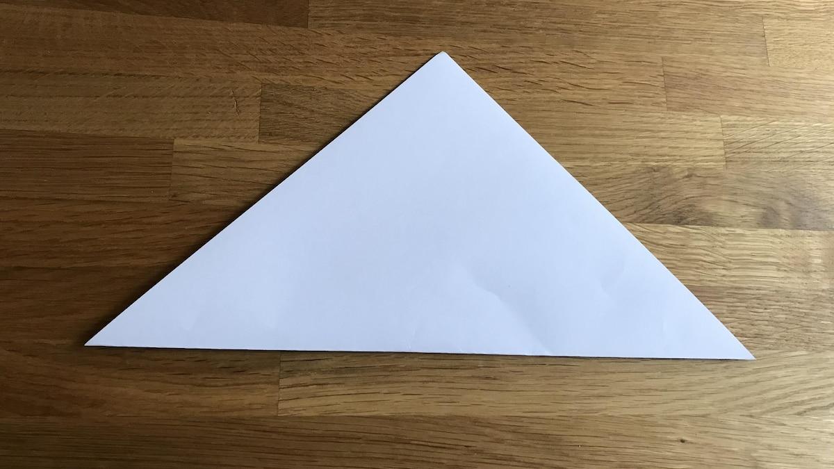 Falten der Origami Schachtel: Im ersten Schritt knicken Sie das Viereck diagonal in der Mitte.