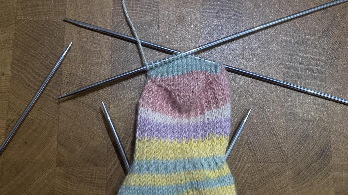 Nehmen Sie Ihre vierte, freie, Nadel und stricken Sie die Hälfte der Käppchen-Maschen rechts.