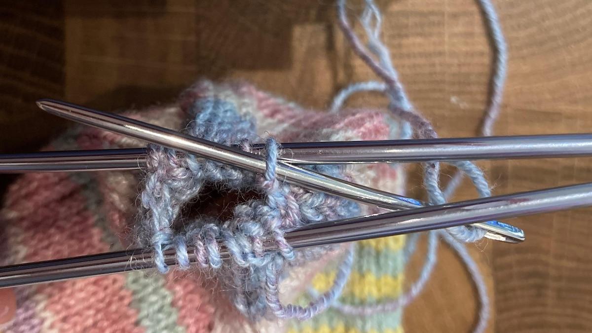 Schritt 3 des Maschenanschlags: stechen Sie von oben in die erste Masche der hinteren Nadel. Schieben Sie die Masche von der Nadel.
