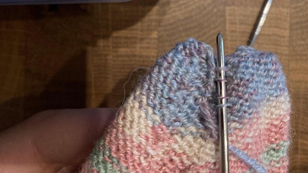 Der Faden der Fußspitze wird auf der Innenseite der Socke vernäht. Achten Sie darauf, immer nur einen Teil jeder Masche aufzustechen.