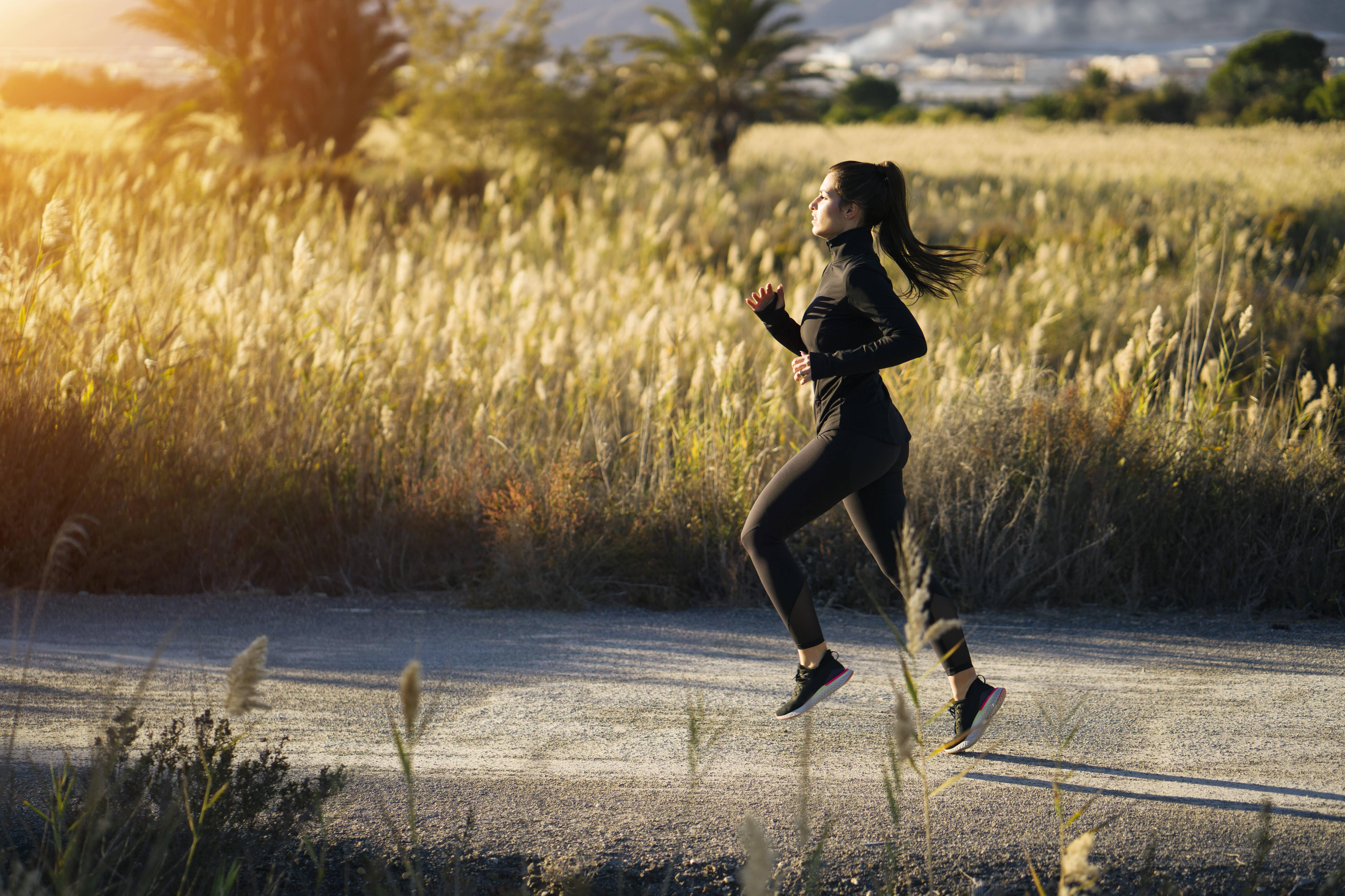 Young woman running on footpath against green landscape at sunset model released Symbolfoto MPPF01351