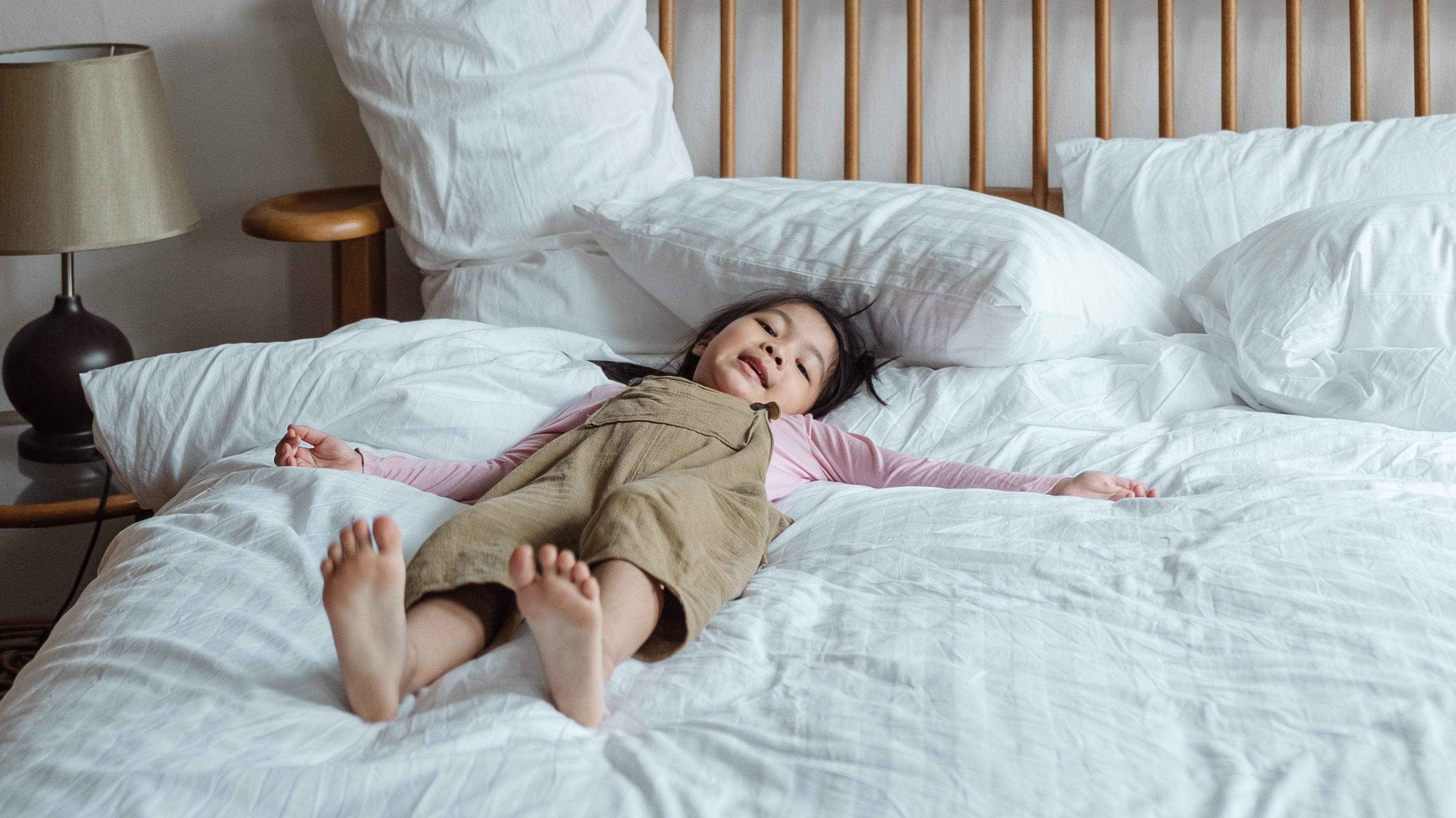 Achtsamkeit für Kinder ist spaßig und entspannend zugleich. Bei Gedankenreisen und Atemübungen sollte die Position gemütlich sein - zum Beispiel im Bett oder auf der Couch.