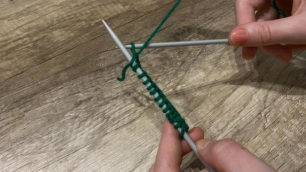 Das Durchziehen hat zu einer neuen Masche auf der rechten Nadel geführt. Entfernen Sie die oberste Masche jetzt von der linken Nadel.