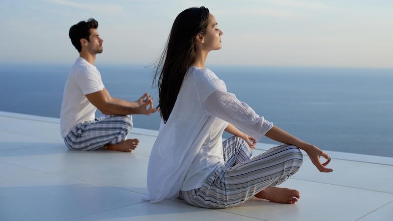 Paar macht Zen Meditation am Meer.