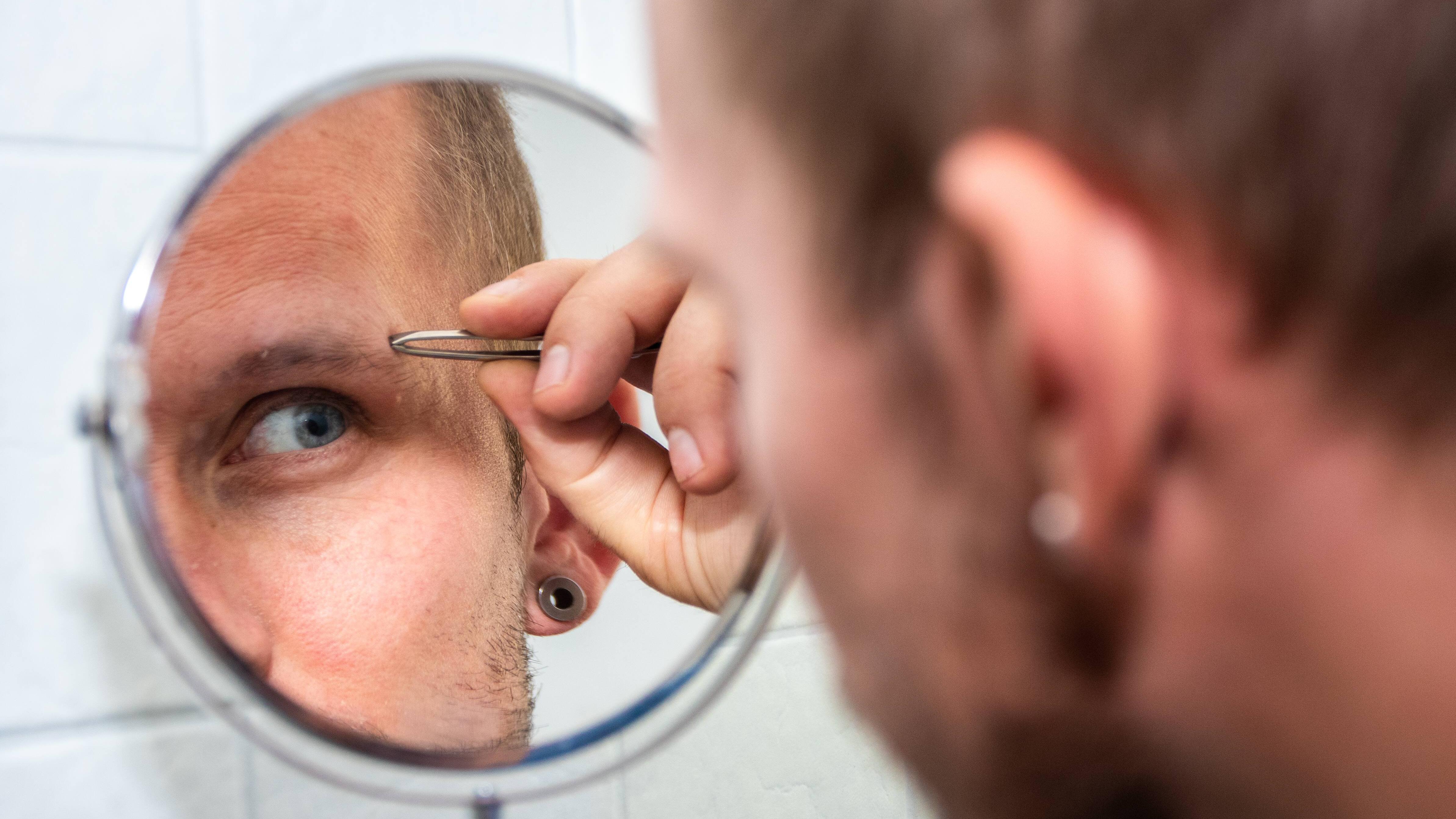 Augenbrauen formen als Mann: Beginnen Sie damit, Ihre Brauen zu stutzen und zu trimmen, um sie anschließend durch das Auszupfen unerwünschter Härchen weiter zu formen.