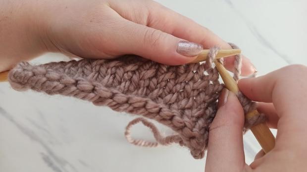 Um verschränkt zu stricken, müssen Sie hinter der Nadel in die Masche einstechen und diese rechts abstricken.