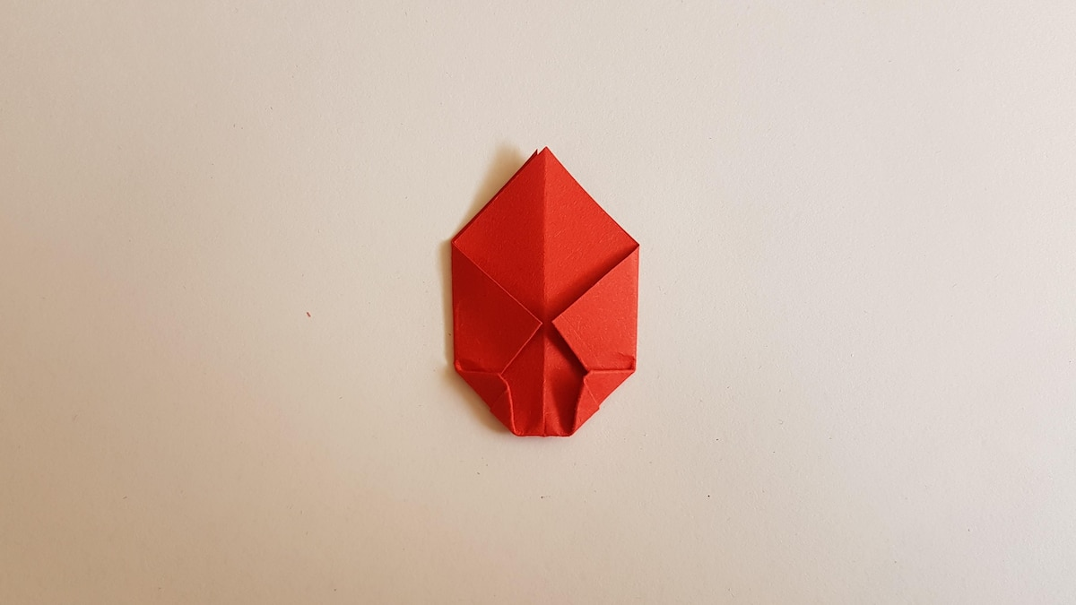 Drehen Sie das Papier um. Falten Sie die Seiten zur mittleren Falzlinie. Klappen Sie danach die unteren Ecken ein wenig nach innen.
