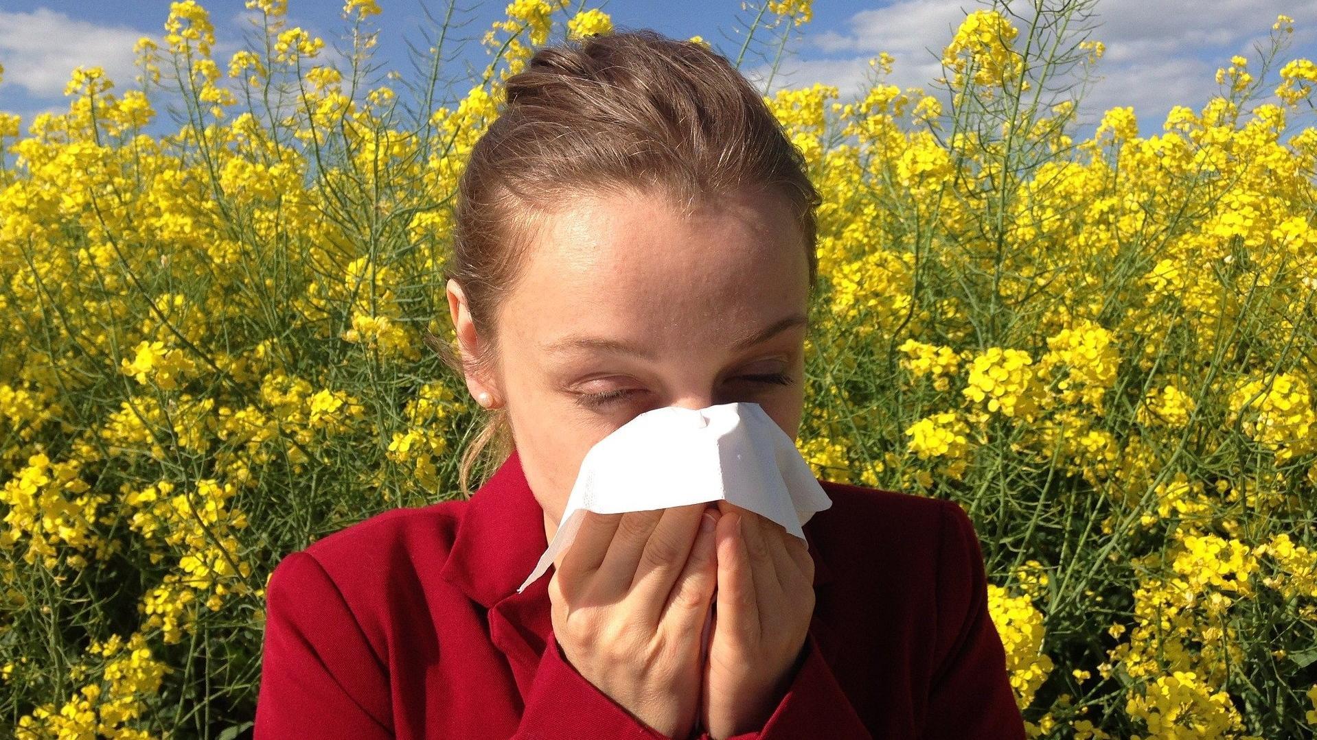 Frau steht vor blühenden Pflanzen und putzt sich die Nase