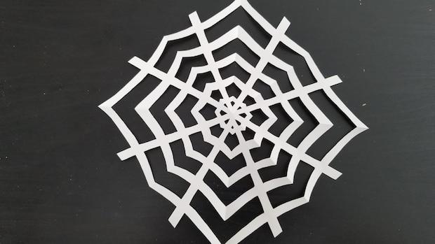 Dekorieren Sie das fertige Spinnennetz mit einer Spinne.
