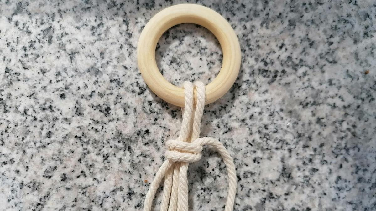 Ziehen Sie an dem Faden oben und unten damit sich der Knoten festigt. Die Enden, die man hier noch sieht, kann man dann abschneiden.