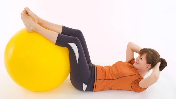 Mit einem Gymnastikball spüren Sie das Wippen auch in den Beinen.