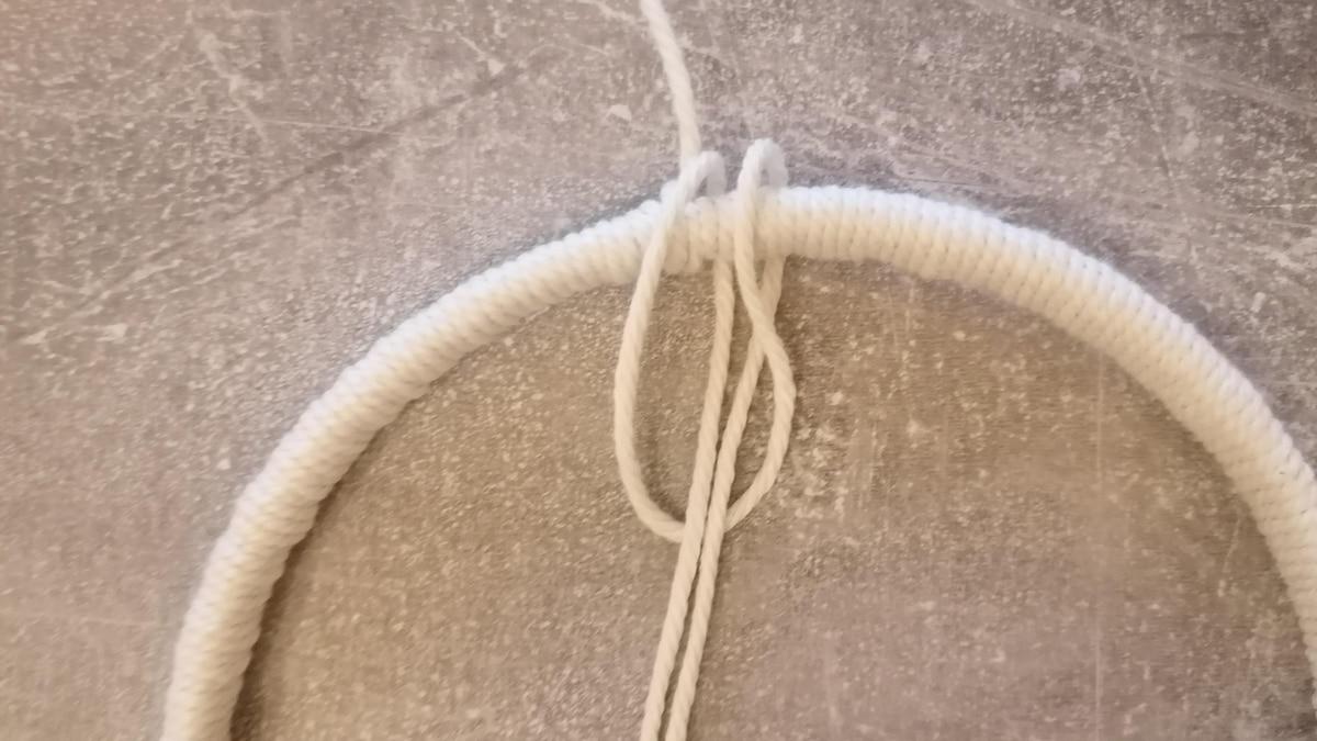 Mithilfe des Ankerknotens werden nun die 10 Fäden am Ring befestigt. Auf dem Bild sehen Sie, wie dieser durchgeführt wird.