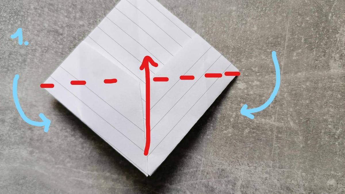 Die blauen Pfeile signalisieren den Schritt vom Dreieck zur Diamantform. Dabei wird das Dreieck vom vorherigen Bild unten aufgeklappt und entgegen der Faltrichtung bisher gefaltet. Im Anschluss folgen Sie dem roten Pfeil und falten zweimal die untere Hälfte nach oben (hinten & vorne).