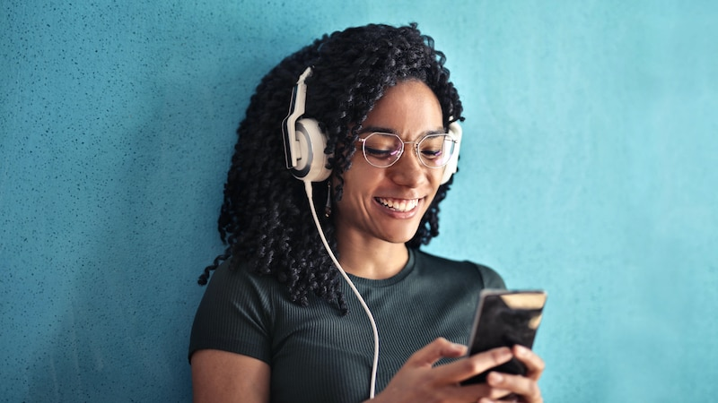 Frau mit Kopfhörern in den Ohren und einem Handy in der Hand