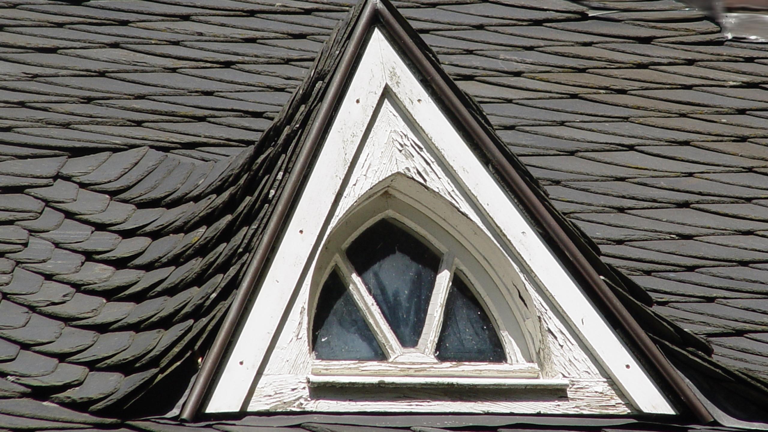 Ein Dreiecksfenster mit Stoff oder einem Rollo verdunkeln