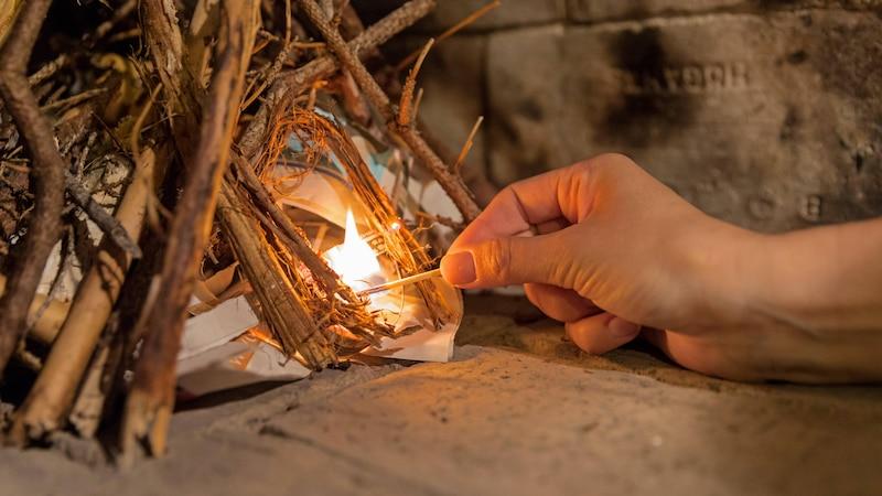 Beim Anzünden von unten ordnen Sie das Brennzholz kegelförmig an. Das hat den Vorteil, dass die dickeren Holzscheite schneller Feuer fangen.