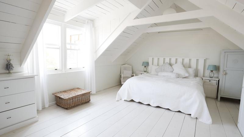 Ein Schlafzimmer mit Dachschräge wirkt offener und freundlicher, wenn Sie die Wände in einer hellen Farbe streichen.