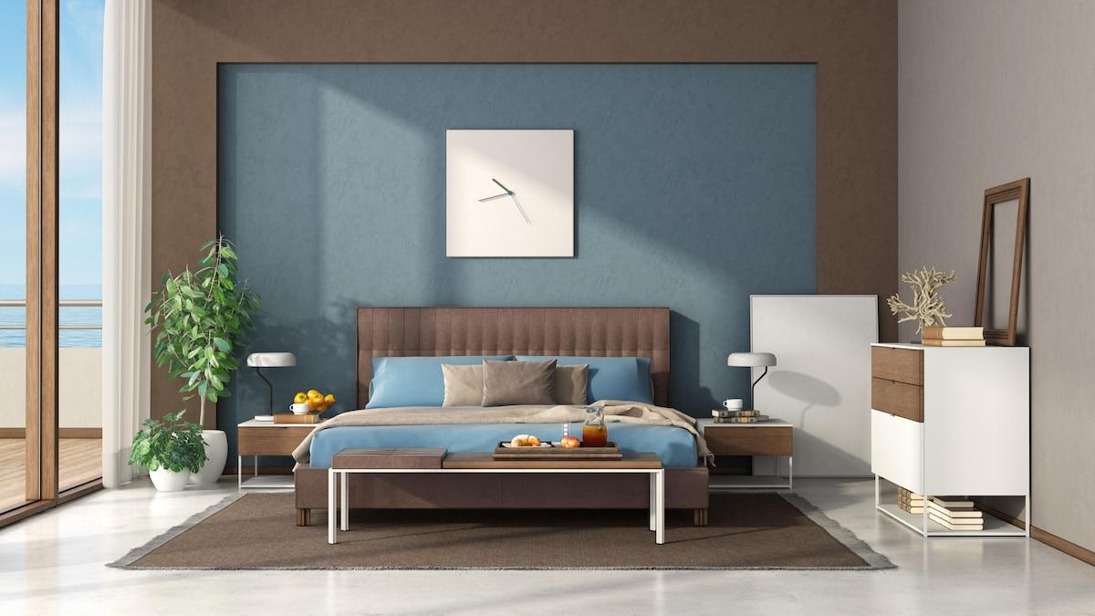 Gestalten Sie die Schlafzimmerwand hinter dem Bett, indem Sie sie fabrlich vom Rest der Wandflächen abheben.