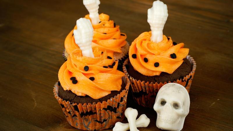 Ideen für Halloween Cupcakes: Schokomuffin mit orangem Frosting und Halloween Dekorationen.