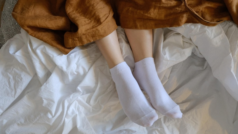 Mit Socken schlafen hat zahlreiche gesundheitliche Vorteile. So bleiben die Füße wärmer, das Einschlafen wird erleichtert und auch die Fußpflege gelingt besser.