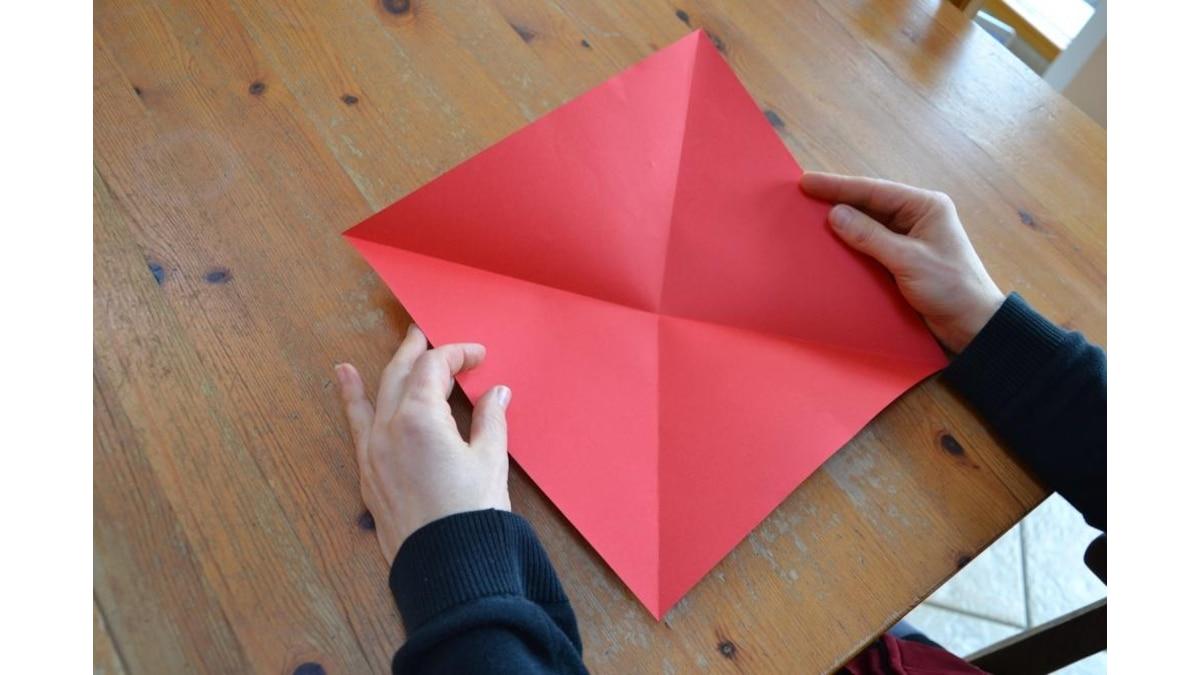 Papier zweimal diagonal falten und wieder aufklappen.