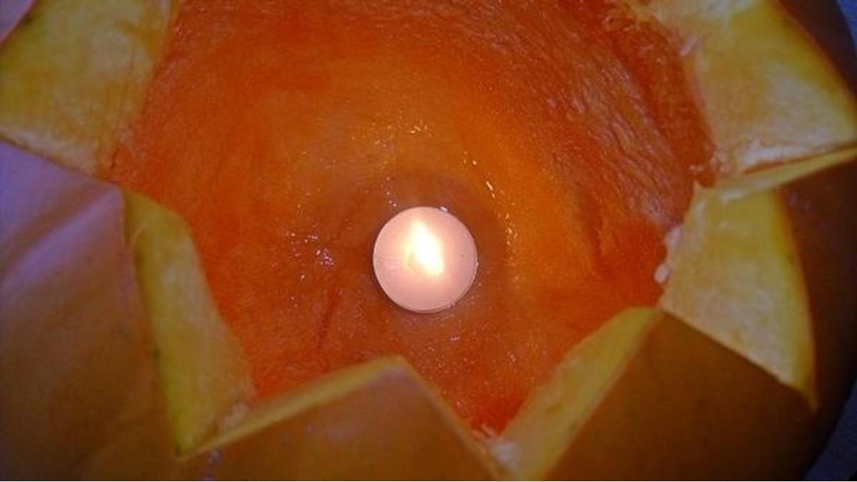 Setzen Sie jetzt ein Teelicht ins Innere des Kürbis und zünden Sie es an. Von außen sehen Sie bereits das leuchtende Kürbis-Gesicht.