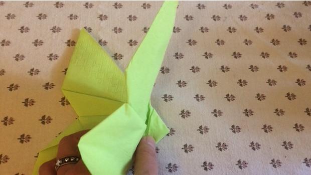 Halten Sie die Serviette an dem kleinen Dreieck und falten Sie die Flügel aus - fertig.
