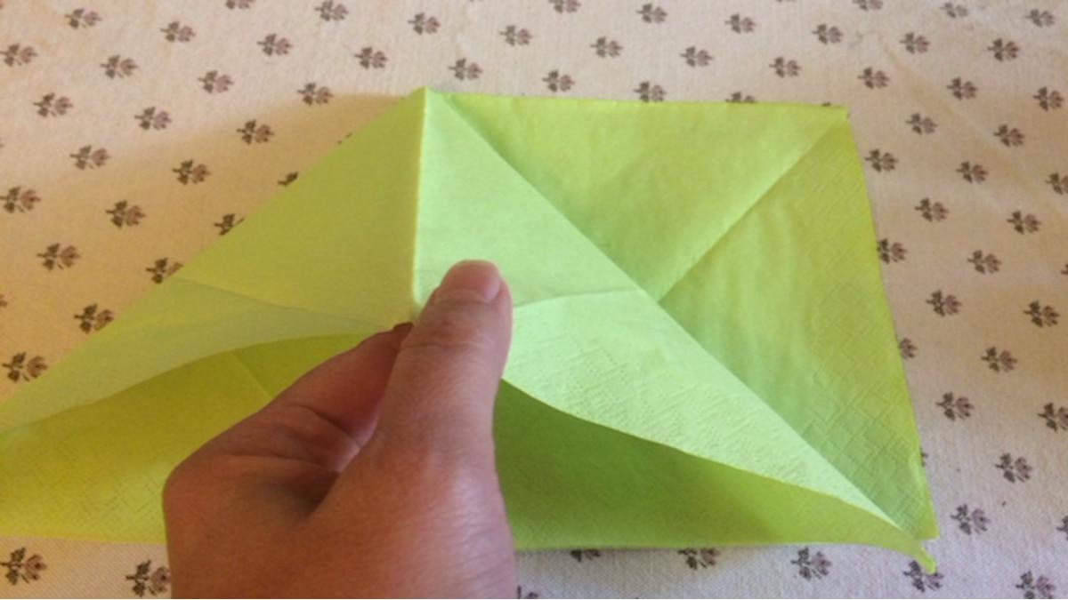Fahren Sie mit der Hand unter die obere Lage und falten Sie aus der einen Seite ein neues Dreieck.