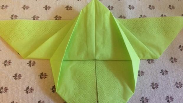 Die Seiten des unteren Dreiecks müssen Sie ein wenig nach innen schlagen und die Falten glattziehen.